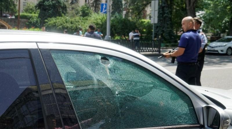 A bullet hole is seen on the window of a car parked in the street in Almaty