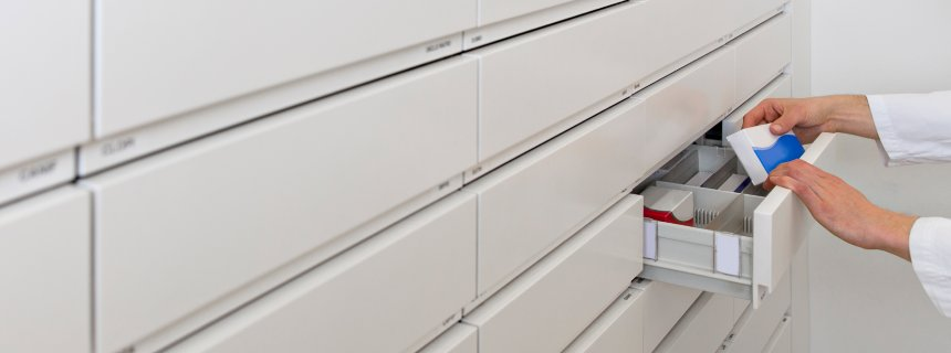Hands of pharmacist taking drug from a drawer cabinet