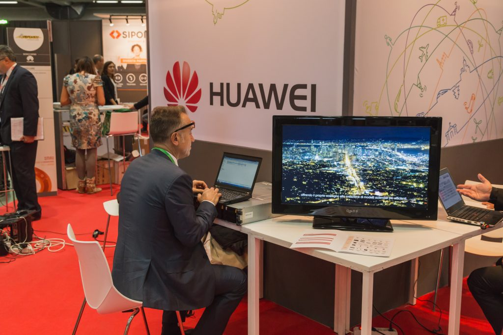 Man working in Huawei stand at Smau 2014 in Milan, Italy